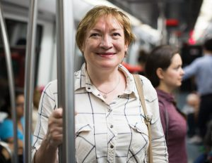 portrait of cheerful retiree woman passenger in public train journey