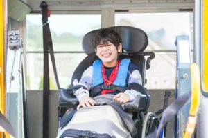 Happy biracial little boy with special needs sitting in wheelchair, riding on yellow school bus lift, going to school